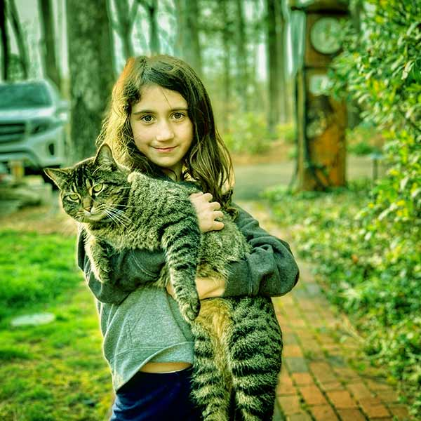 Image of Jodi's daughter, Charlie holding a grey cat on her arm